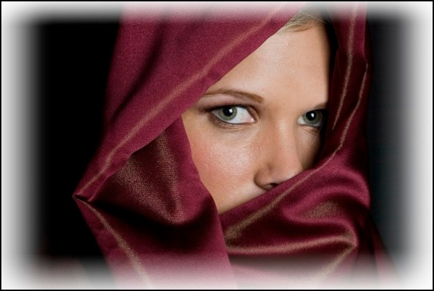 Mystery woman in red veil with beautiful green eyes