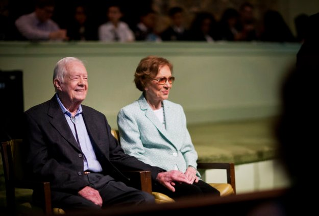 Former President Jimmy Carter, left, sits with his wife Rosalynn as they wait to pose for photos after Carter taught Sunday School class at Maranatha Baptist Church in his hometown, Sunday, Aug. 23, 2015, in Plains, Ga. More than 700 people heard Carter deliver a familiar message this weekend: When your burden grows heavy, ask God for strength. (AP Photo/David Goldman)